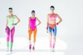 smiling sporty girls exercising at aerobics workout on grey