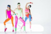 beautiful athletic girls in 80s style sportswear exercising together on grey