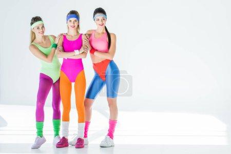 belles jeunes femmes sportives dans les années 80 style sportswear, souriant à la caméra sur fond gris
