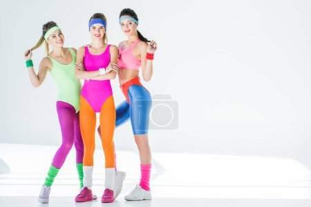 full length view of beautiful athletic girls in 80s style sportswear smiling at camera on grey