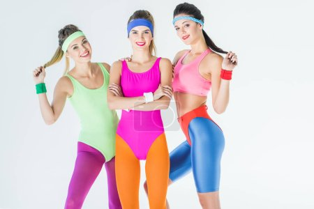 beautiful athletic girls in 80s style sportswear smiling at camera isolated on grey