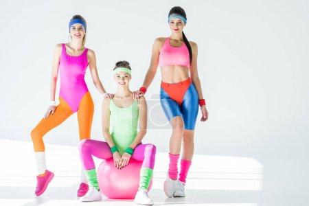 Athlétisme jeunes femmes dans les années 80 style sportswear, souriant à la caméra sur fond gris
