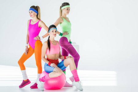 athletic young women in 80s style sportswear posing together on grey