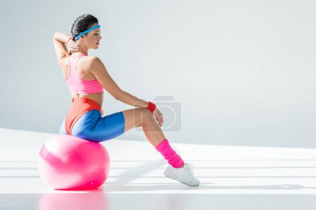 Photo for Athletic young woman sitting and exercising on fitness ball on grey - Royalty Free Image