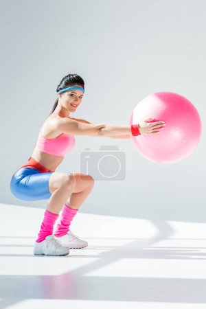 attractive young woman training with fitness ball and smiling at camera on grey