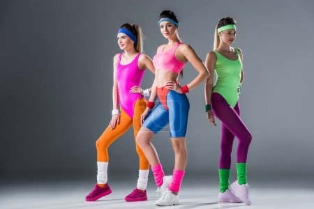 attractive sporty girls in 80s style sportswear posing together on grey