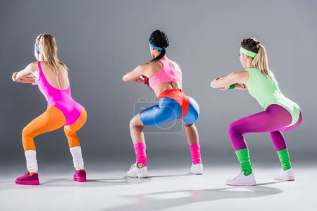 rear view of sporty young women doing squat together on grey