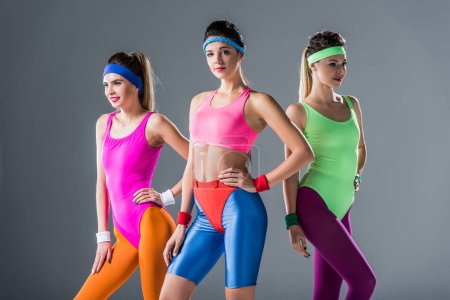 beautiful sporty girls in 80s style sportswear posing together isolated on grey