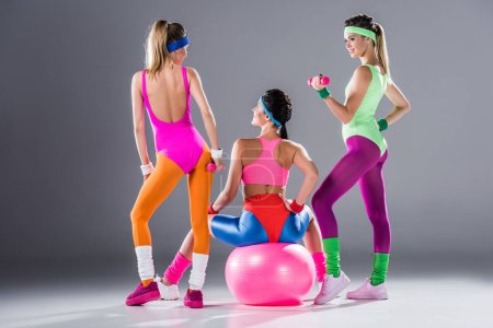 back view of sporty young women with dumbbells and fit ball training on grey