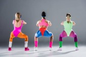 back view of sporty young women in 80s style doing squats on grey