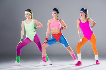 beautiful sporty young women training at aerobics workout on grey