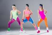 beautiful sporty young women training at aerobics workout on grey