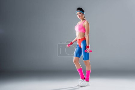 beautiful sporty girl holding dumbbells and smiling at camera on grey