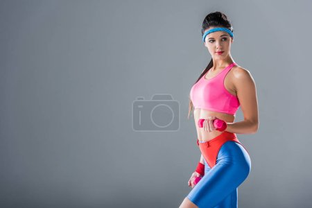 sporty young woman training with dumbbells and looking away isolated on grey