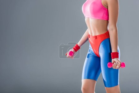 cropped shot of sporty young woman training with dumbbells isolated on grey
