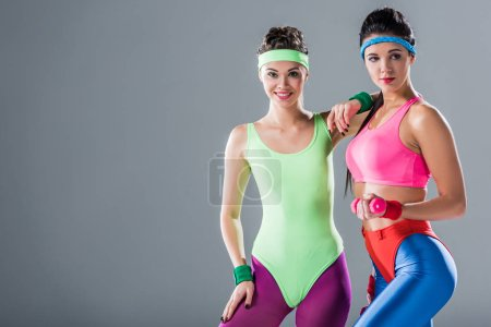 beautiful sporty young women posing together at aerobics workout isolated on grey