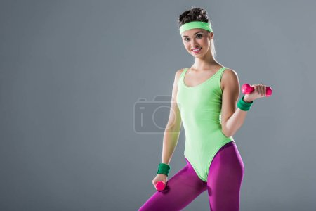 sporty girl training with dumbbells and smiling at camera isolated on grey