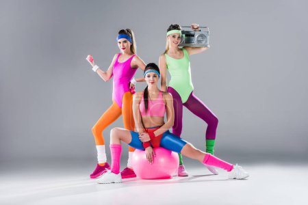 happy sporty girls with sports equipment and tape recorder on grey