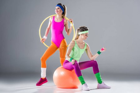 smiling sporty girls training with hula hoop, dumbbell and fit ball on grey