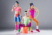 sporty young women with hula hoop, dumbbells, fit ball and bottle of water on grey
