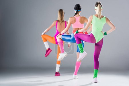 Photo for Back view of sporty young women exercising together on grey - Royalty Free Image