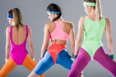 back view of sporty girls training at aerobics workout isolated on grey