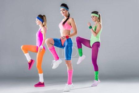 Foto de Hermosas chicas deportivas entrenamiento juntos en gris - Imagen libre de derechos