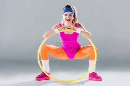 happy young sportswoman exercising with hula hoop and smiling at camera on grey