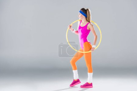 Photo for Full length view of smiling sporty woman training with hula hoop on grey - Royalty Free Image