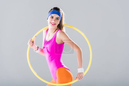 Photo for Smiling sporty girl training with hula hoop isolated on grey - Royalty Free Image