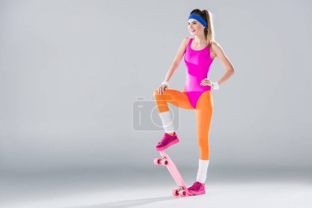 smiling young sportswoman posing with penny board and looking away on grey