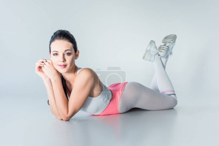 beautiful young sportswoman lying and smiling at camera on grey