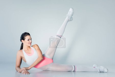 beautiful smiling young woman exercising and looking away on grey