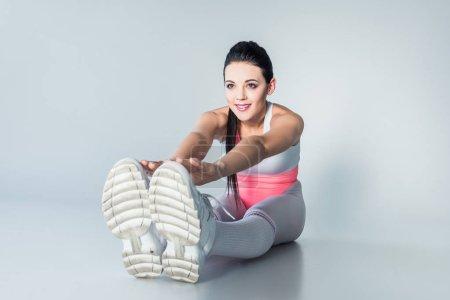 Foto de Sonriente a niña deportiva estiramientos y mirando lejos en gris - Imagen libre de derechos