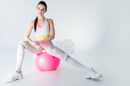 Photo for Beautiful smiling sportswoman sitting on fit ball and looking away on grey - Royalty Free Image
