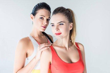 belles jeunes femmes sportives debout ensemble isolé sur gris