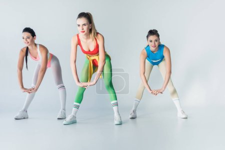 attractive sporty girls in bodysuits training together on grey