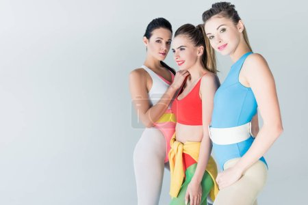 beautiful sporty girls in bodysuits standing together isolated on grey