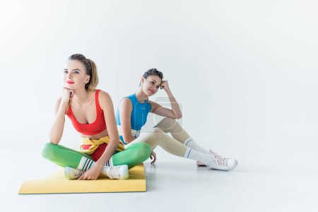 beautiful smiling sporty girls sitting on yoga mat and looking away on grey
