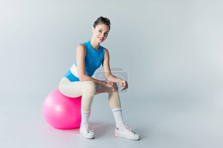 Photo for Beautiful sporty girl sitting on fitness ball and smiling at camera on grey - Royalty Free Image