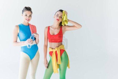 belles jeunes femmes sportives tenant la serviette et bouteille d'eau après la séance d'entraînement isolé sur fond gris