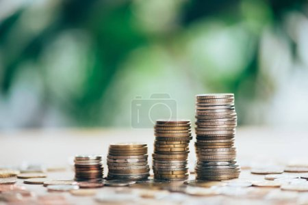 close-up view of stacked coins on table and blurred background