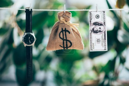 sackcloth bag, wristwatch and dollar banknote hanging on rope