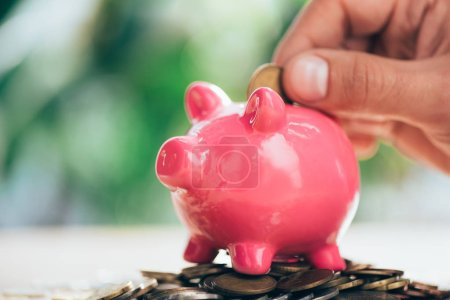 close-up partial view of person putting coin into pink piggy bank