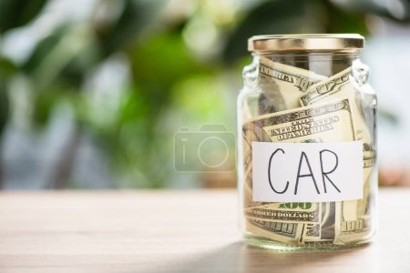 close-up view of glass jar with dollar banknotes and inscription car