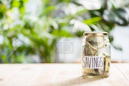 Photo pour Vue rapprochée du bocal en verre avec billets en dollars et économies d'inscription - image libre de droit