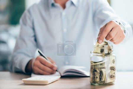 partial view of man working and putting dollar banknote in glass jar