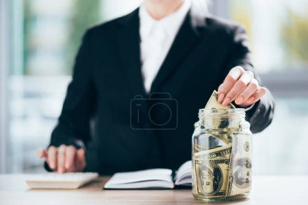 cropped shot of businesswoman working and putting dollar banknote in glass jar