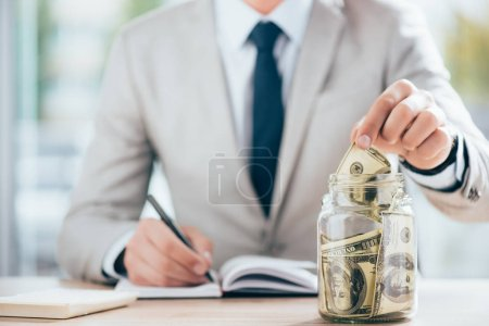 cropped shot of businessman working and putting dollar banknote in glass jar
