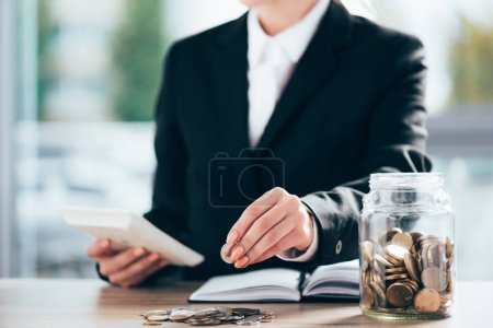 cropped shot of businesswoman working and putting coin on pile